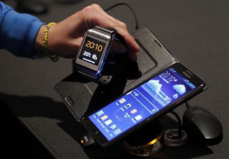 Un periodisa observa el reloj Galaxy Gear de Samsung junto a un teléfono Galaxy Note 3 de la misma firma, durante su lanzamiento en Berlín, sep 4 2013